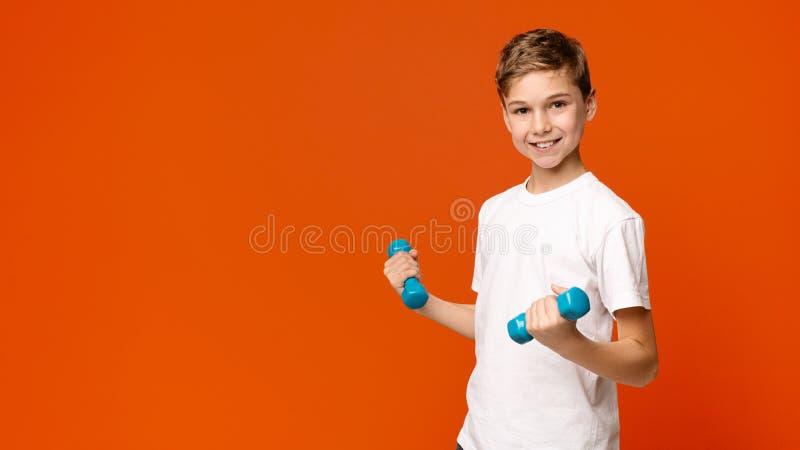 Menino alegre que exercita com pesos, fundo alaranjado imagens de stock royalty free