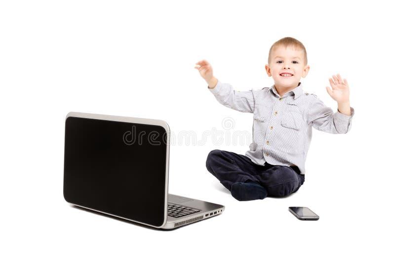 Menino alegre que senta-se antes de um portátil foto de stock