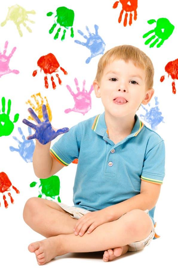 Menino alegre que senta-se com pintado à mão fotos de stock royalty free
