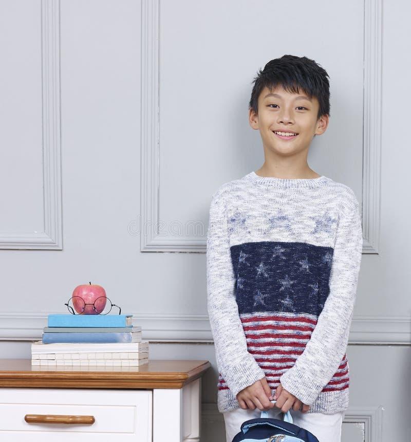 Menino asiático adolescente de sorriso que guarda o saco de livro que está ao lado da mesa fotos de stock