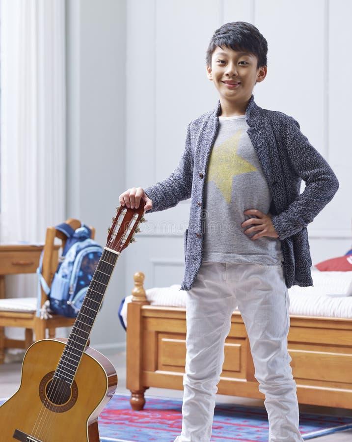 Menino asiático adolescente que guarda a guitarra, levantando & sorrindo no quarto fotografia de stock royalty free