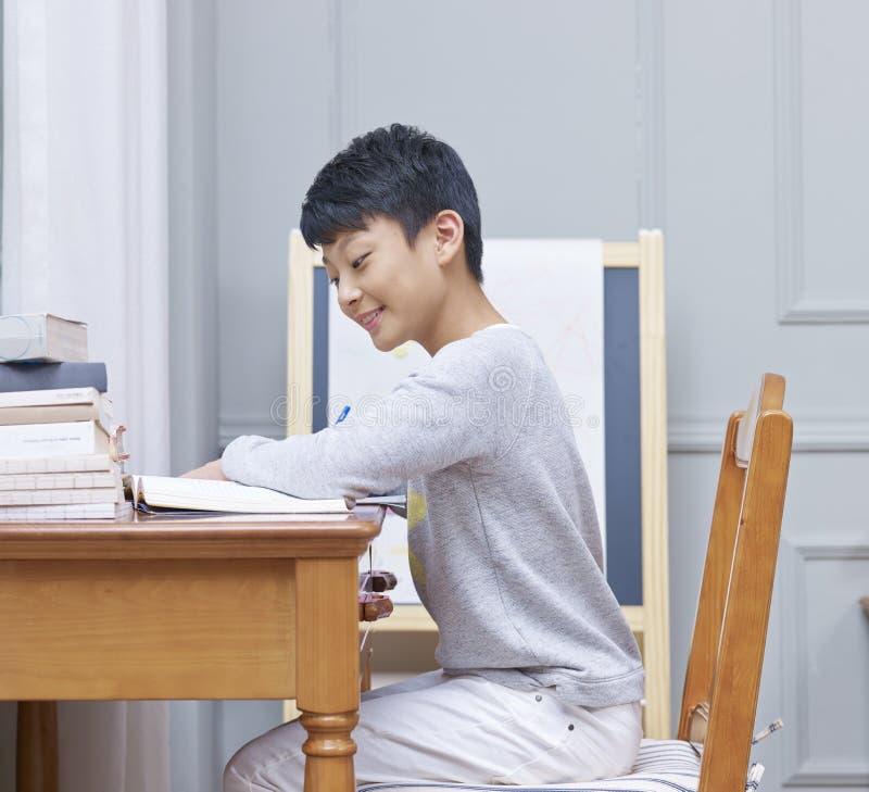 Menino asiático adolescente que sorri, aprendendo & fazendo trabalhos de casa em casa imagem de stock royalty free