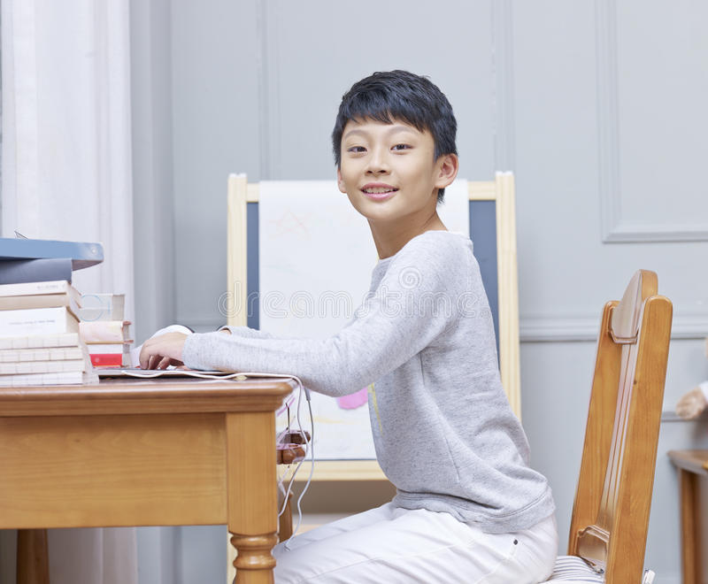 Menino asiático adolescente que sorri, olhando a câmera & surfando a rede imagem de stock royalty free