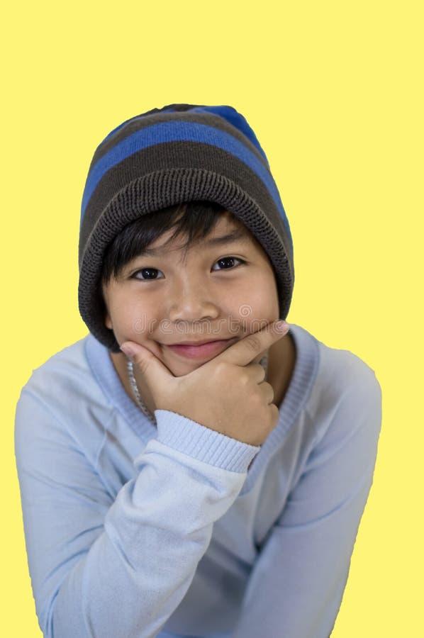 Menino asiático bonito, vestindo um tampão azul e uma camisa sleeved longa, sorrindo felizmente, e levantando sua mão sob o queix foto de stock royalty free