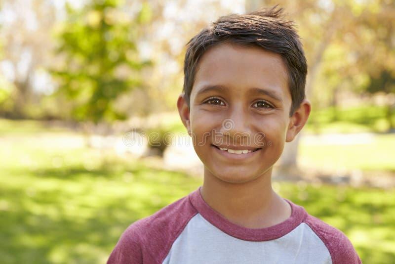 Menino asiático caucasiano da raça misturada no parque que olha à câmera imagens de stock