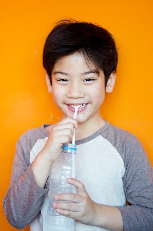 Menino asiático com a garrafa da água imagem de stock royalty free