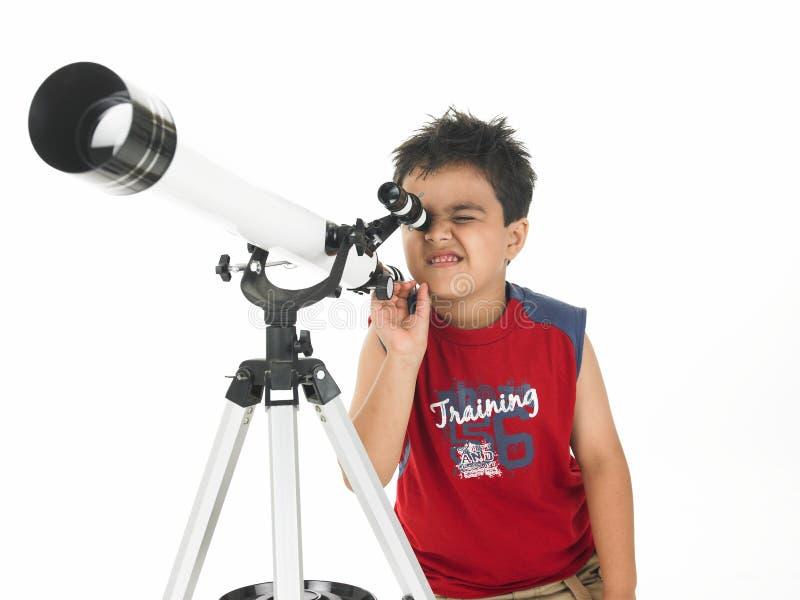 Menino asiático com um telescópio foto de stock royalty free