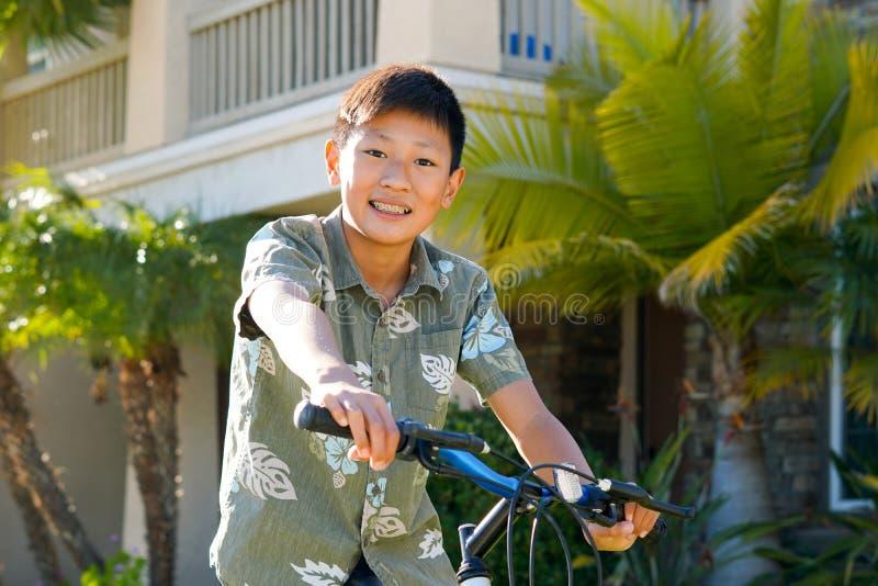 Menino asiático da criança com as cintas em sua bicicleta na frente da casa fotografia de stock
