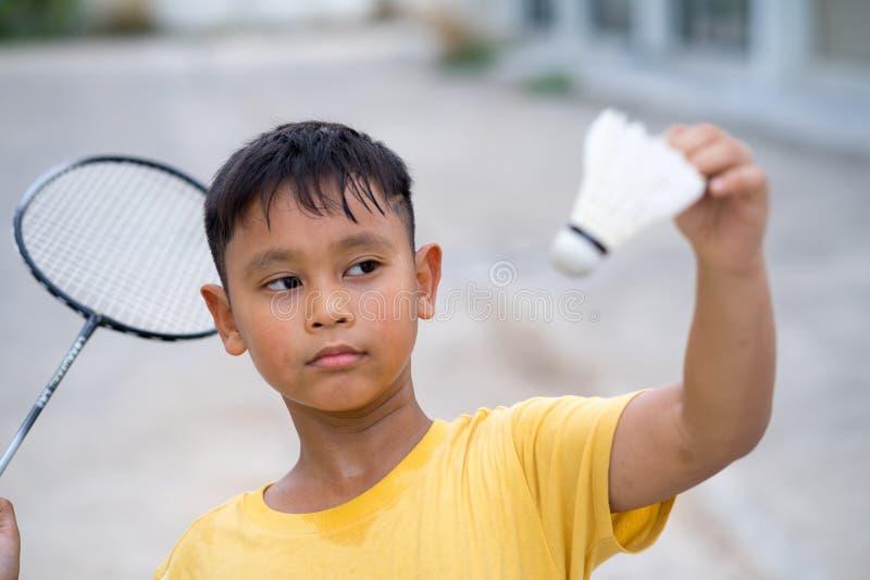 Menino asiático da criança que joga o badminton em casa fotografia de stock