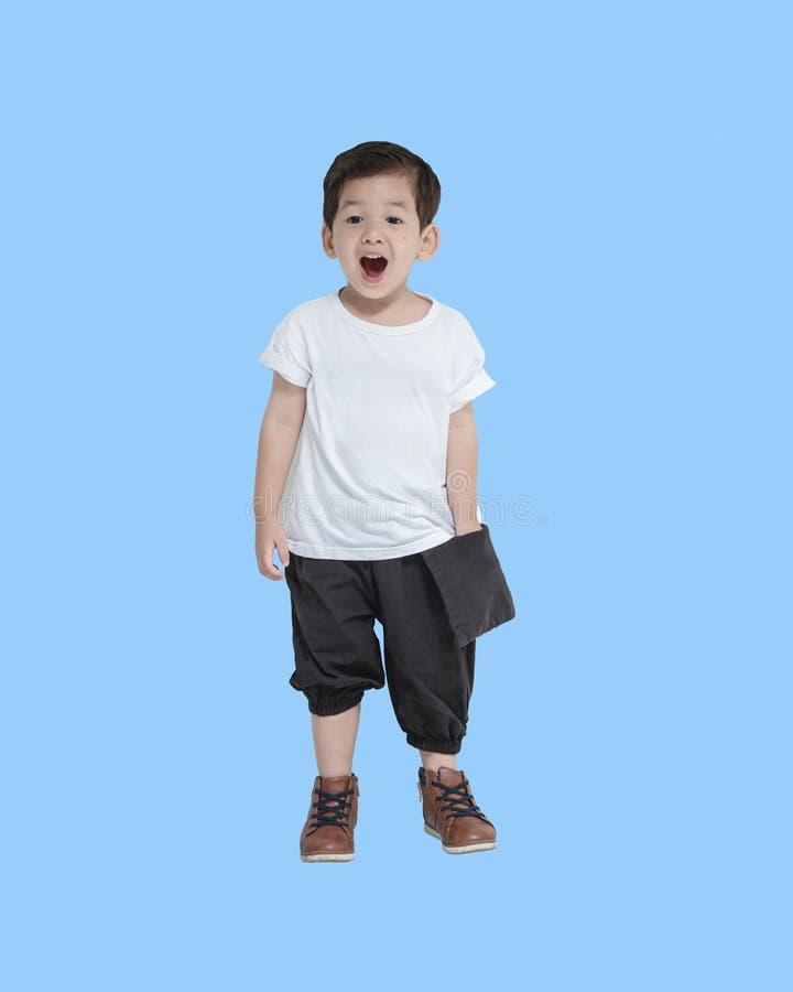 Menino asiático do close up na emoção feliz isolado no fundo azul imagens de stock
