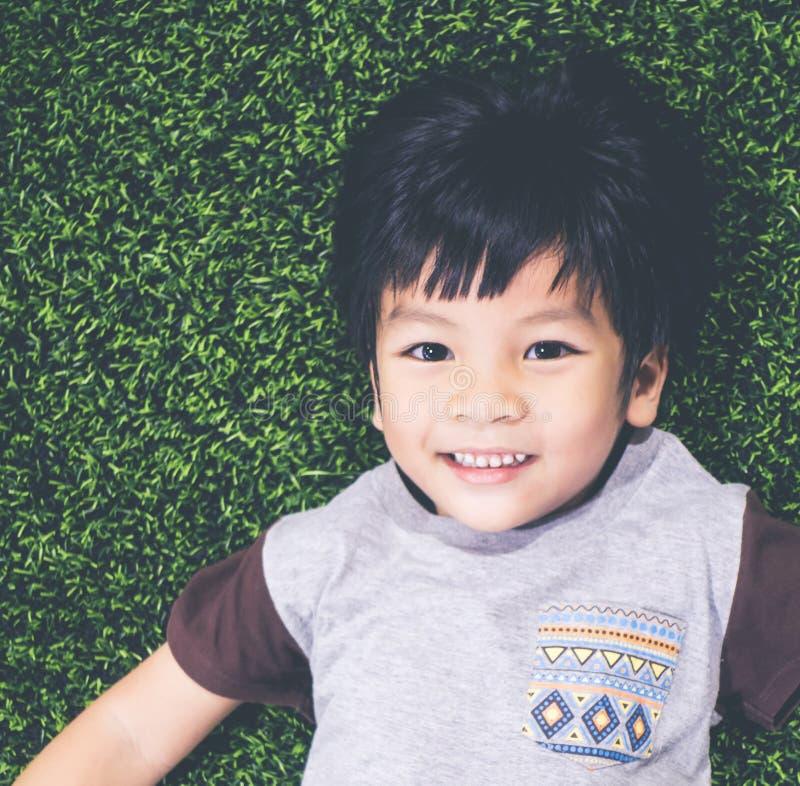 Menino asiático feliz de sorriso que encontra-se para baixo no assoalho da grama foto de stock