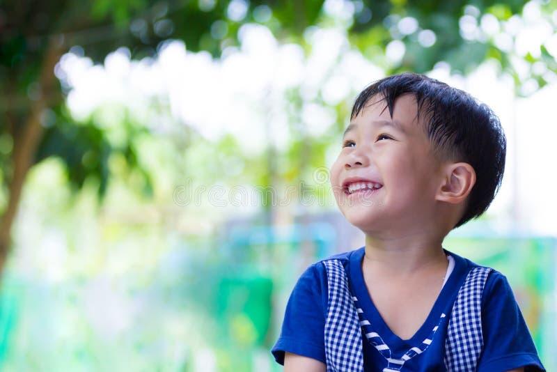 Menino asiático feliz que olha acima no parque Fora no tempo do dia, tr imagens de stock