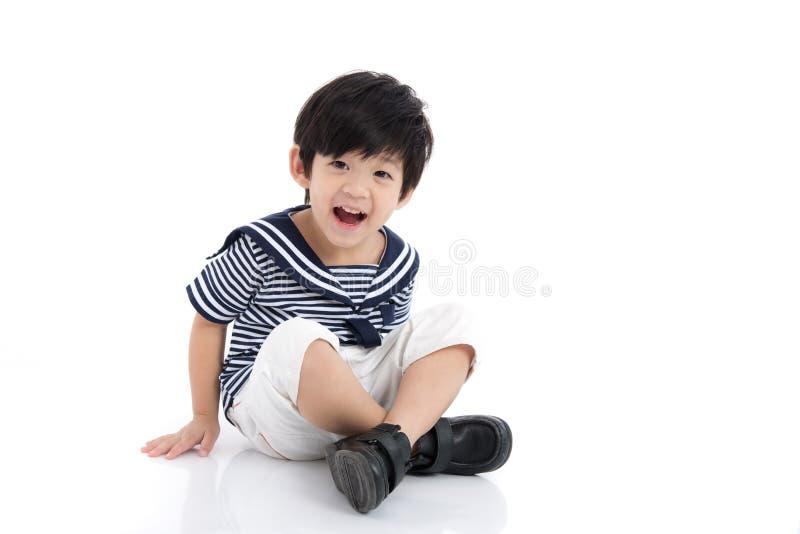 Menino asiático feliz que senta-se no fundo branco imagem de stock royalty free