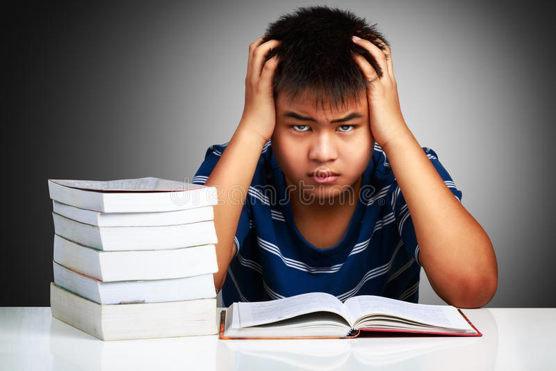 Menino asiático irritado com dificuldades de aprendizagem fotos de stock