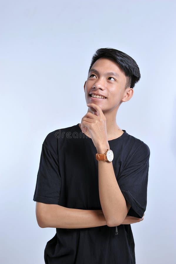 Menino asiático novo considerável que veste o t-shirt e o relógio de pulso pretos com mão no queixo que pensa sobre a pergunta, e foto de stock