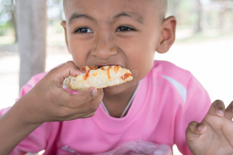 Menino asiático pequeno bonito que come o petisco fotos de stock royalty free