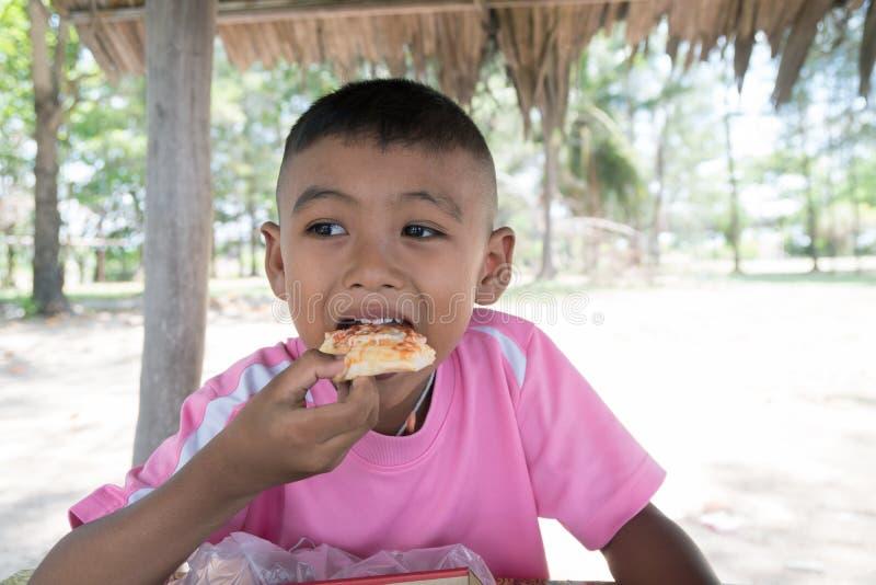Menino asiático pequeno bonito que come o petisco fotografia de stock