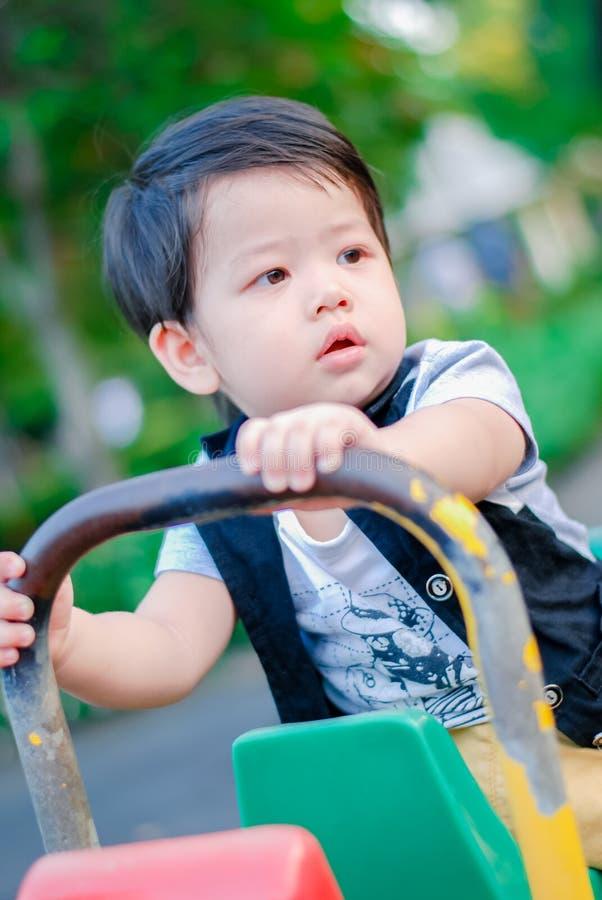 Menino asiático pequeno bonito que tem o divertimento em um campo de jogos fora, crianças felizes foto de stock royalty free