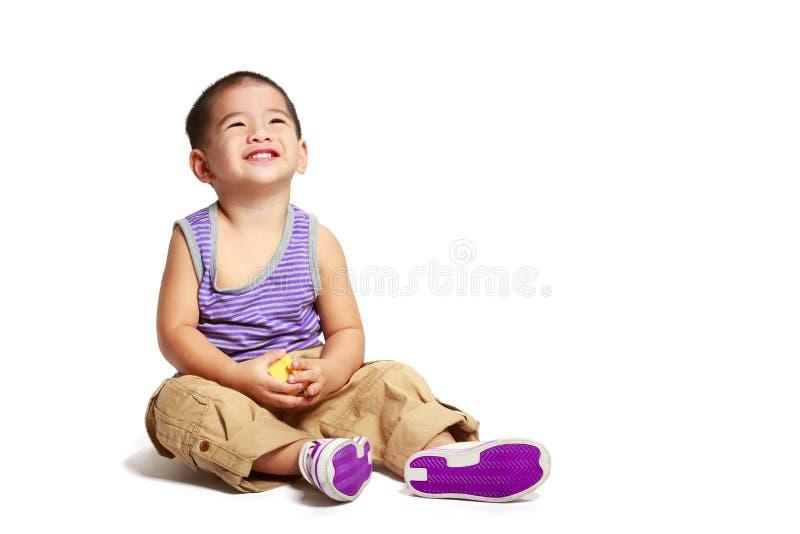Menino asiático pequeno de sorriso que senta-se no assoalho fotografia de stock royalty free