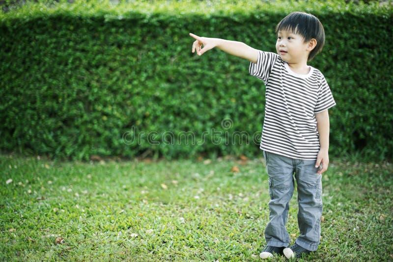 Menino asiático pequeno que está e que aponta seu dedo imagens de stock