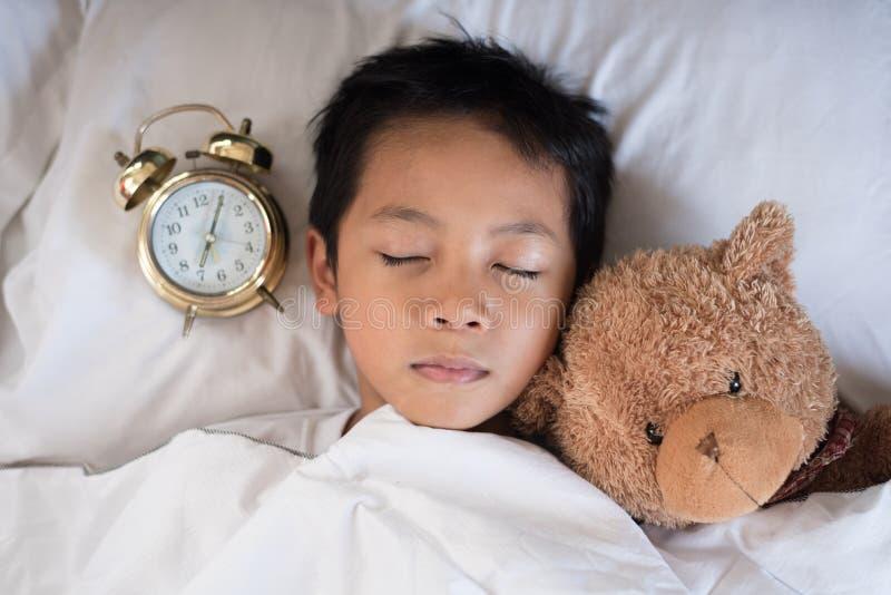 Menino asiático que dorme no descanso e na folha brancos da cama com o urso do despertador e de peluche fotos de stock royalty free