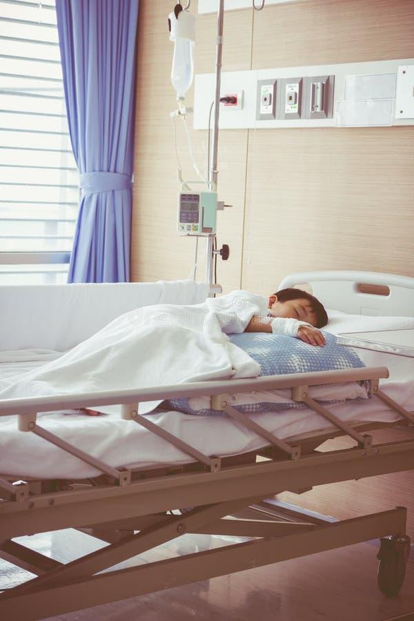 Menino asiático que encontra-se no leito do enfermo com intravenous salino (iv) saúde fotografia de stock