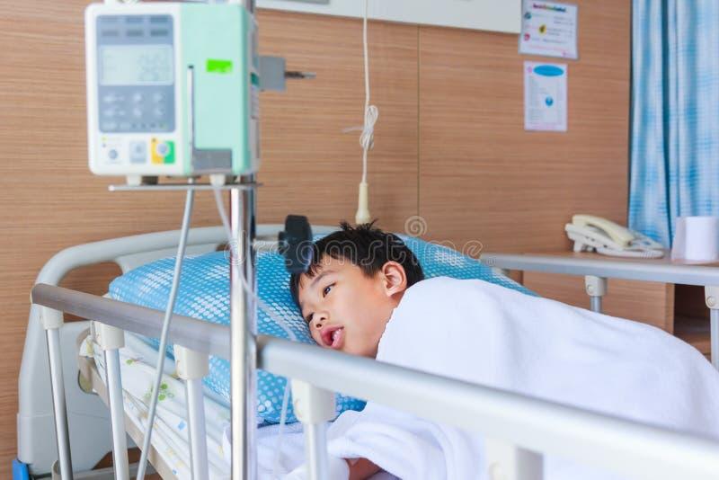 Menino asiático que encontra-se no leito do enfermo com o dri do intravenous IV da bomba da infusão imagens de stock