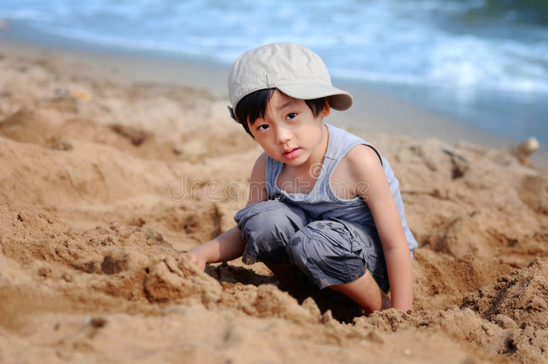Menino asiático que joga na praia fotografia de stock