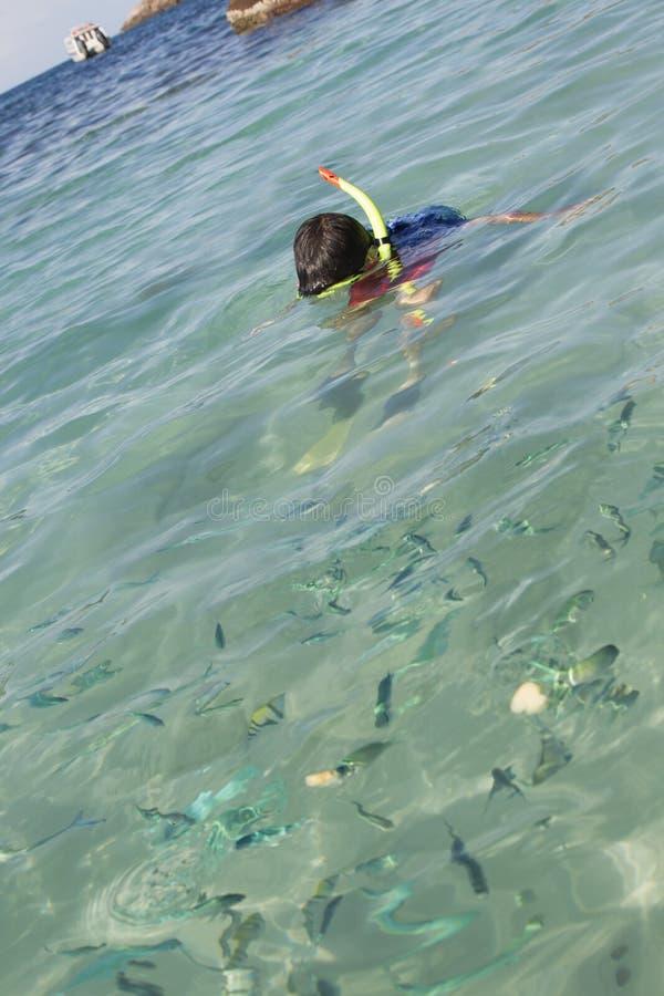 Menino asiático que mergulha na água do mar clara foto de stock