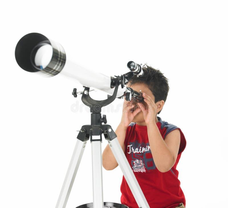 Menino asiático que olha através de um telescópio imagem de stock royalty free