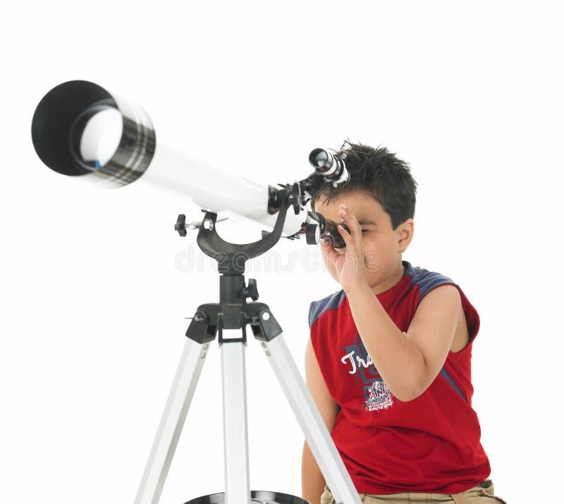 Menino asiático que olha através de um telescópio fotos de stock royalty free