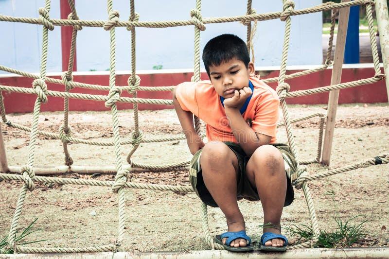Menino asiático que senta-se apenas no campo de jogos fotos de stock royalty free