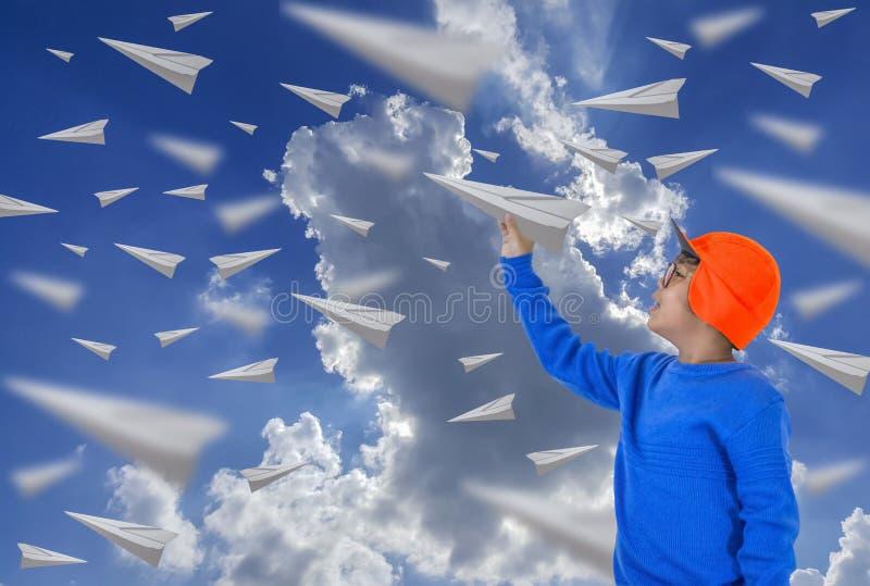 Menino asiático, vidros vestindo, chapéu alaranjado e camisa azul longa Jogando um avião de papel imagem de stock