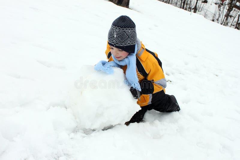 Menino ativo que faz a bola de neve para o boneco de neve fotografia de stock royalty free