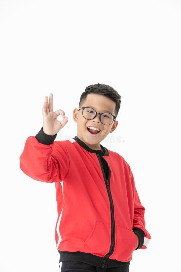 Menino bonito asiático do retrato que mostra o gesto aprovado isolado em b branco fotos de stock