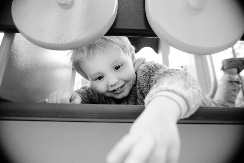 Menino bonito ativo da criança que tem o divertimento no campo de jogos imagens de stock