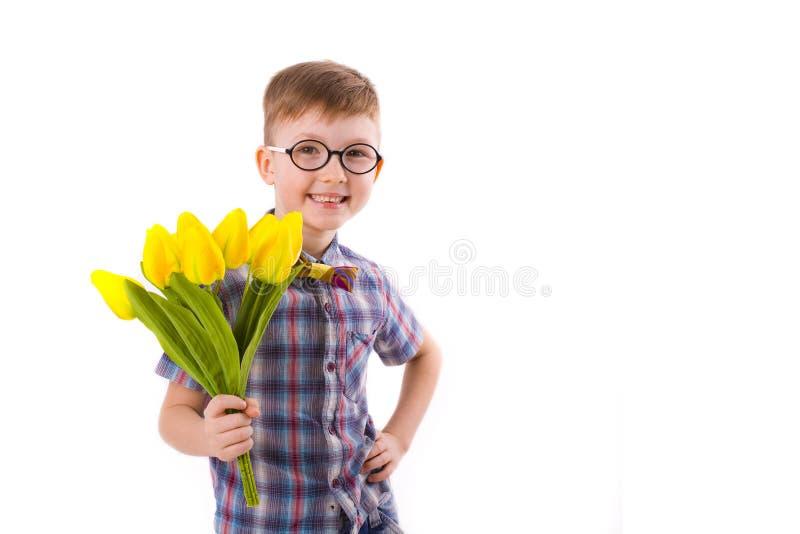 Menino bonito cinco anos, com o ramalhete das tulipas fotografia de stock