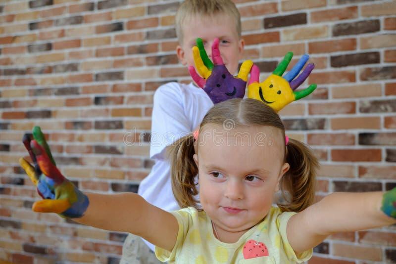 Menino bonito com as mãos pintadas que jogam com sua irmã mais nova em casa imagem de stock