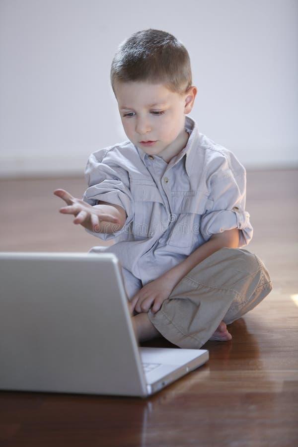 Menino bonito com computador portátil imagens de stock royalty free