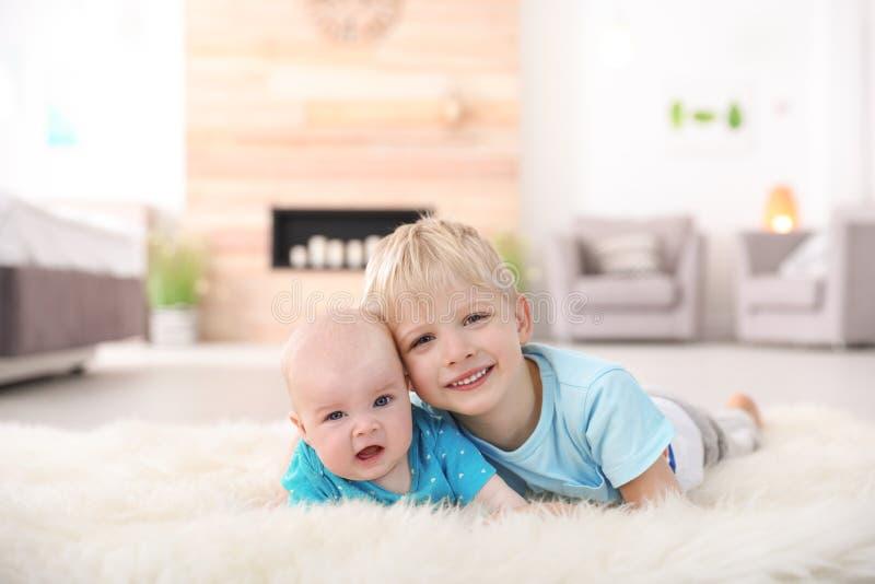 Menino bonito com sua irmã mais nova que encontra-se no tapete da pele foto de stock royalty free