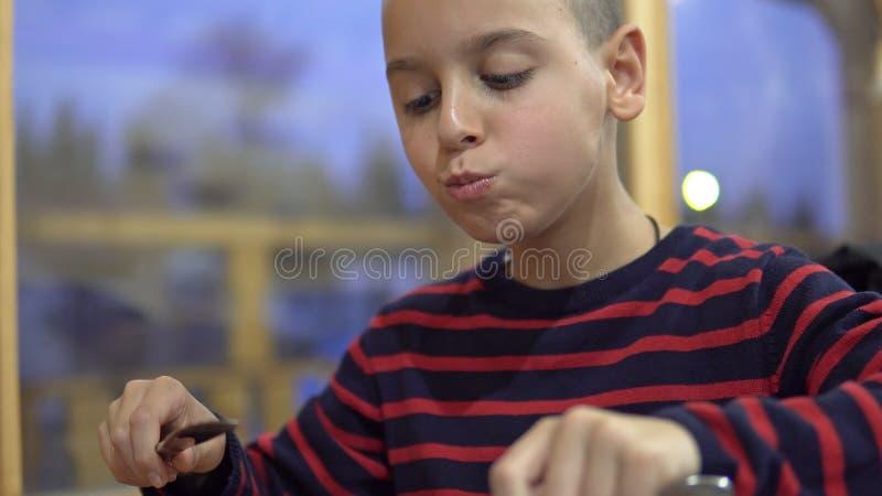 Menino bonito, comendo panquecas no restaurante fotos de stock royalty free