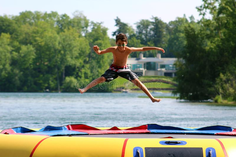 Menino bonito considerável que salta em um trampolim da água que flutua em um lago em Michigan durante o verão imagens de stock