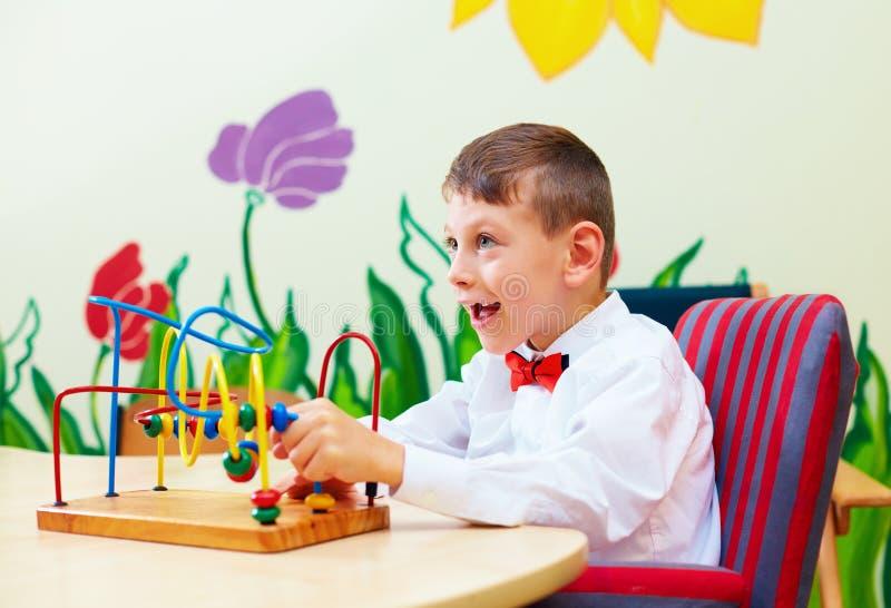 Menino bonito, criança na cadeira de rodas que resolve o enigma lógico no centro de reabilitação para crianças com necessidades e imagem de stock