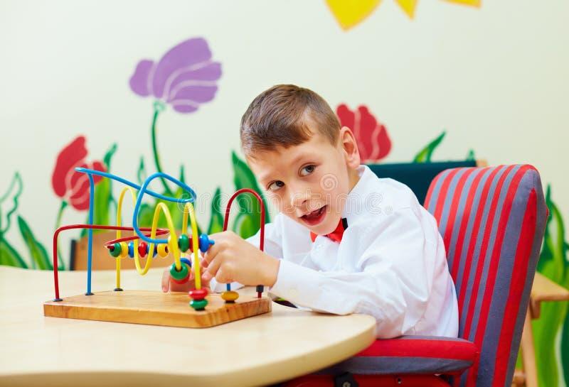 Menino bonito, criança na cadeira de rodas que resolve o enigma lógico no centro de reabilitação para crianças com necessidades e imagem de stock royalty free