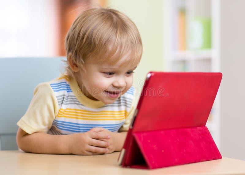 Menino bonito da criança da criança com PC da tabuleta imagem de stock royalty free
