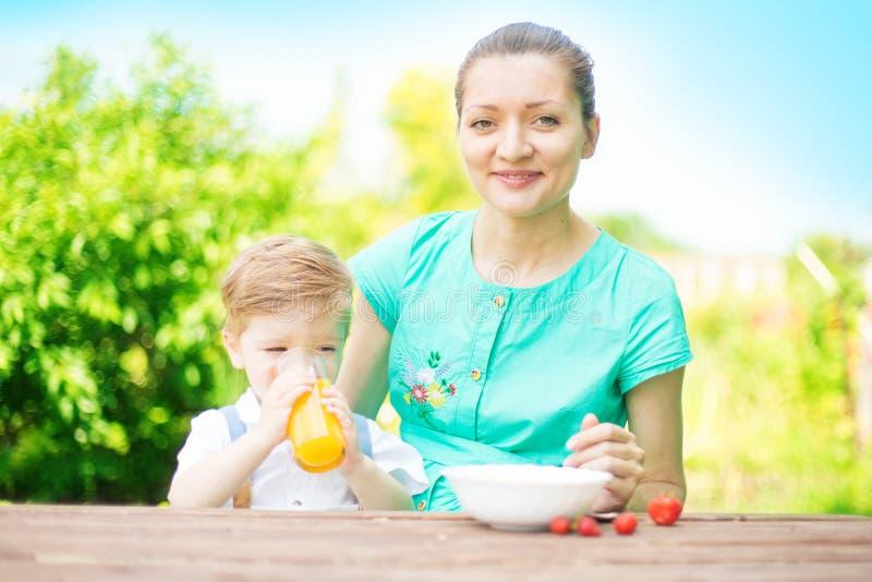 Menino bonito da criança que bebe um vidro do suco de laranja fresco O menino está bebendo o suco de laranja Família feliz que re fotos de stock