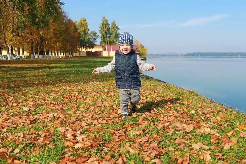 Menino bonito da criança que corre no outono fora fotos de stock royalty free