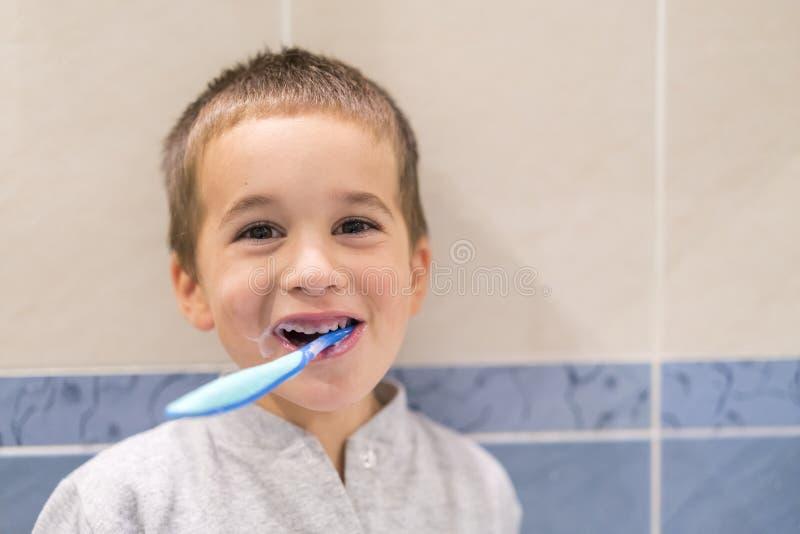 Menino bonito da criança que escova seus dentes no banheiro Criança que aprende como ficar saudável Conceito dos cuidados médicos fotos de stock