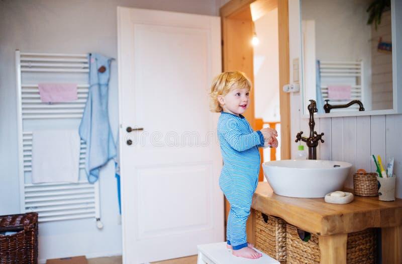Menino bonito da criança que está em um tamborete no banheiro imagem de stock royalty free