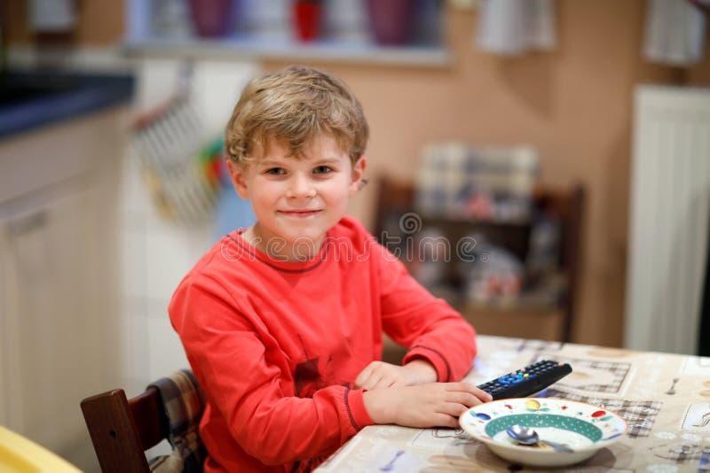 Menino bonito da criança que olha a tevê na noite antes de ir para a cama Criança feliz saudável que tem o divertimento com desen fotografia de stock